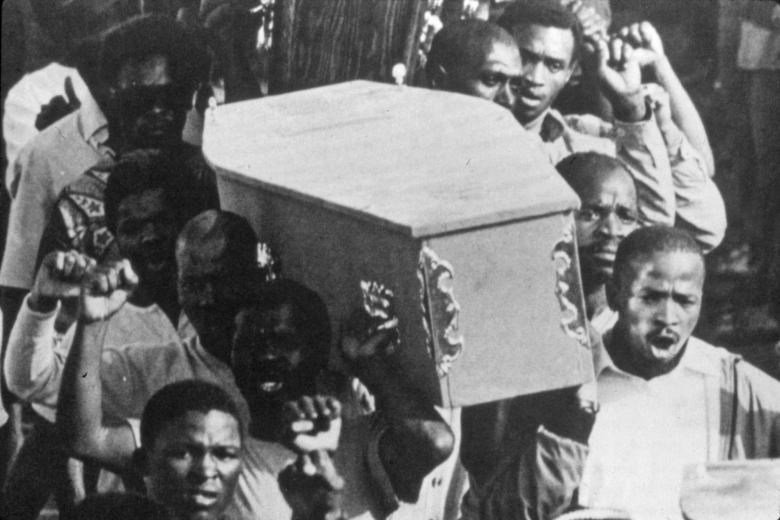 Men hold up fists as they carry a casket.
