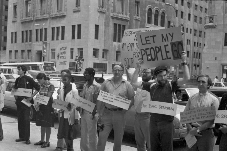Group of people stand on the sidewalk, holding signs.