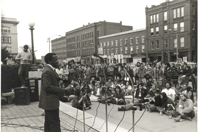 Man speaks to a large group of people seated and standing on the sidewalk.