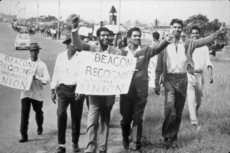 Group of men walk together holding signs and with hands raised in celebration.