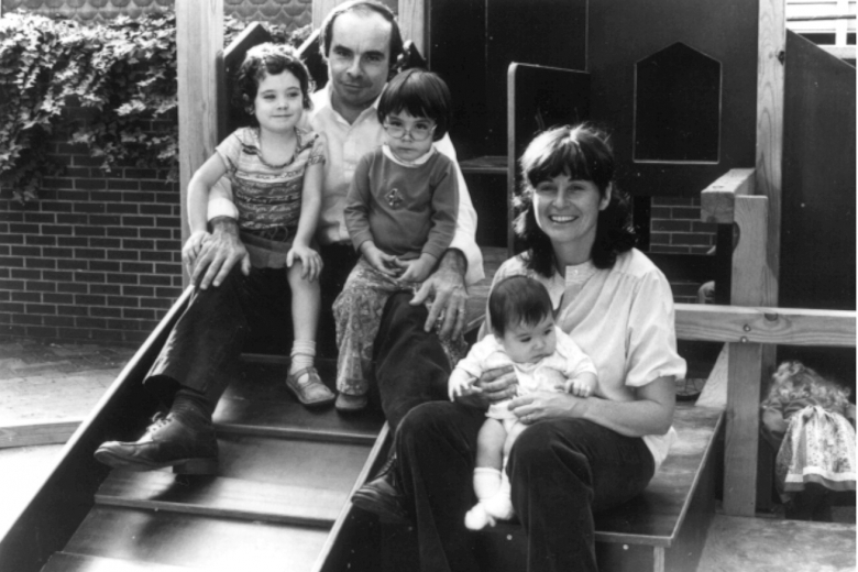 Man and woman sit on the steps to a building holding three children.