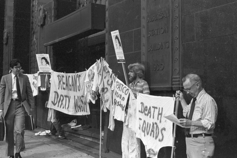 Line of people hold signs in front of a building as a man walks by on the sidewalk.
