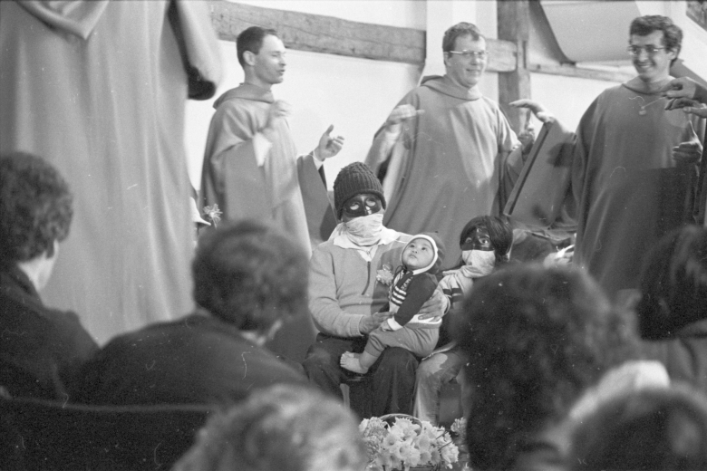 Three men wearing robes walk near two people wearing a masks, one holding a baby.