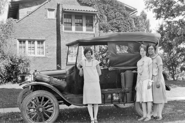 Three women standing in front of a car.