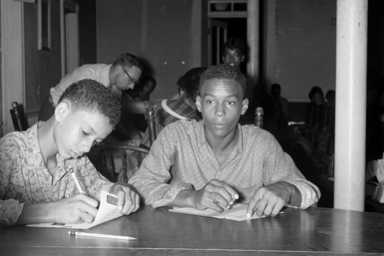 Two young men do schoolwork at a table with teacher behind, working with other students.