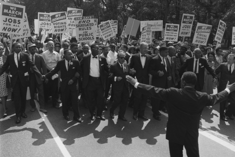 Man walks backwards, arms outstretched, in front of a large group of people marching, signs in hand.