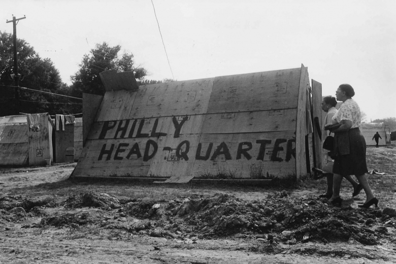 """Two women walk by a building made of plywood with the words """"Philly head-quarter"""" painted on the side."""