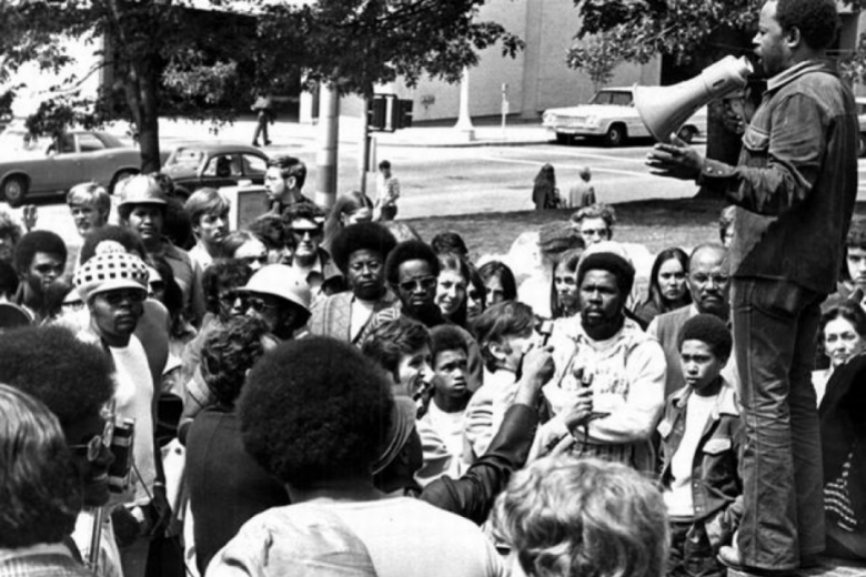Man standing on a step above a crowd speaks into a megaphone.