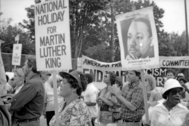 Group of people cheer and clap while holding signs referencing Dr. Martin Luther King.