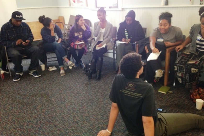 Young adults sitting in chairs and on the ground in a circle.