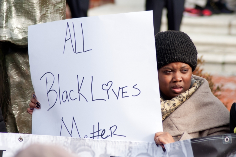 """Woman holds a sign that says """"All Black Lives Matter"""""""