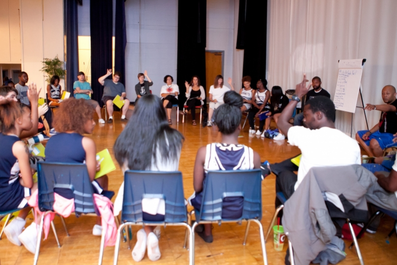 Young people seated in chairs in a circle talk with one another.