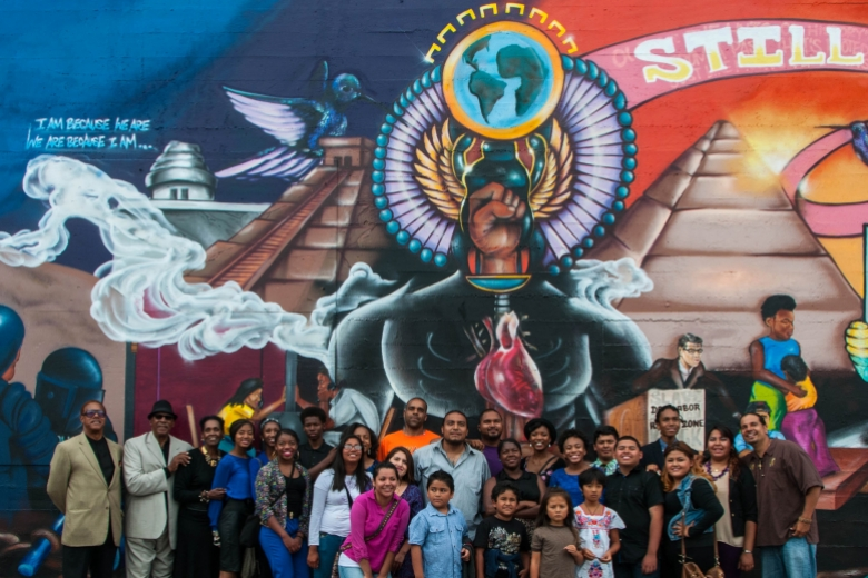 Multi-age group stands in front of a colorful mural.