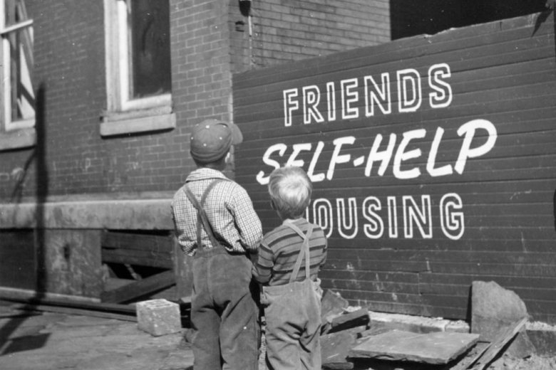 "Two people stand, looking at a sign painted on a wall that reads ""Friends Self-Help Housing."""