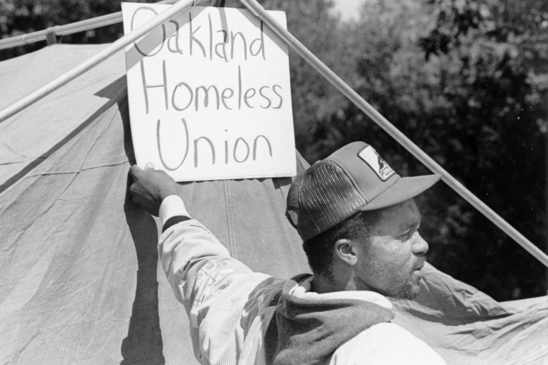"Man stands next to a tent and holds up a sign that reads ""Oakland Homeless Union."""