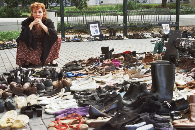 Woman squats next to many pairs of civilian shoes lined up outside.