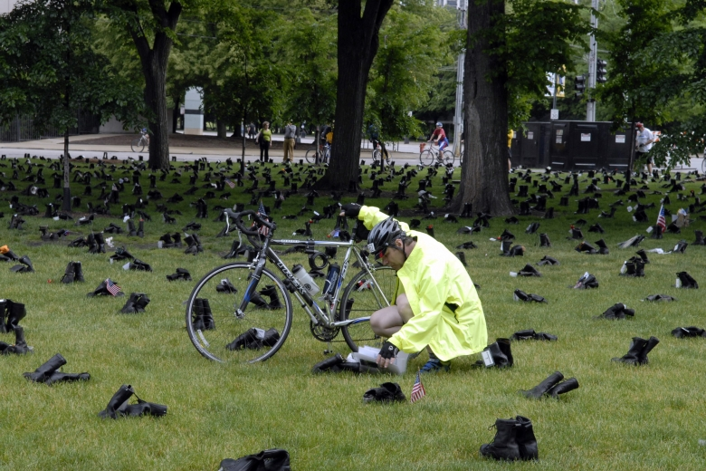 Person holding a bike kneels near a pair of boots to read something.