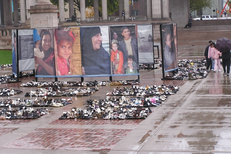 Collections of civilian shoes fill the space in front of large photos of Iraqis who had been killed in the war.