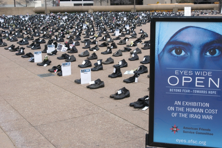"Rows and columns of boots fill a large public area and a sign in front reads ""Eyes Wide Open."""