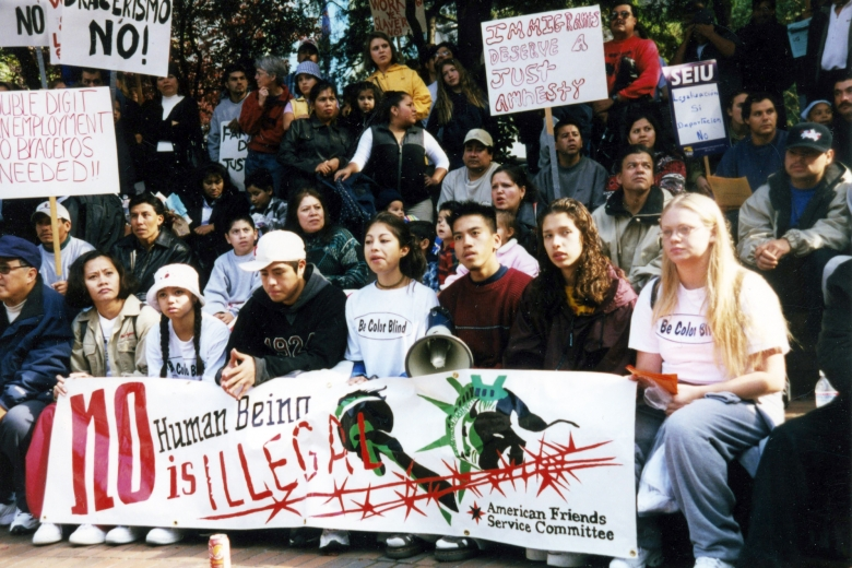 Young adults sit and stand together in a large group holding megaphones and signs.