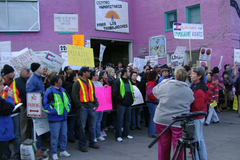 Large group of protesters stand, holding signs, in front of a building with purple walls.