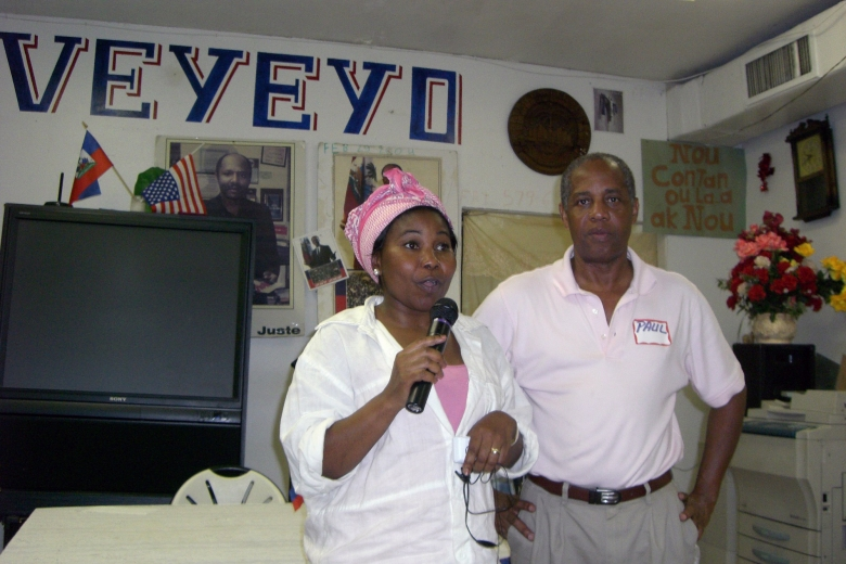 Man and woman stand together as the woman speaks into a microphone.