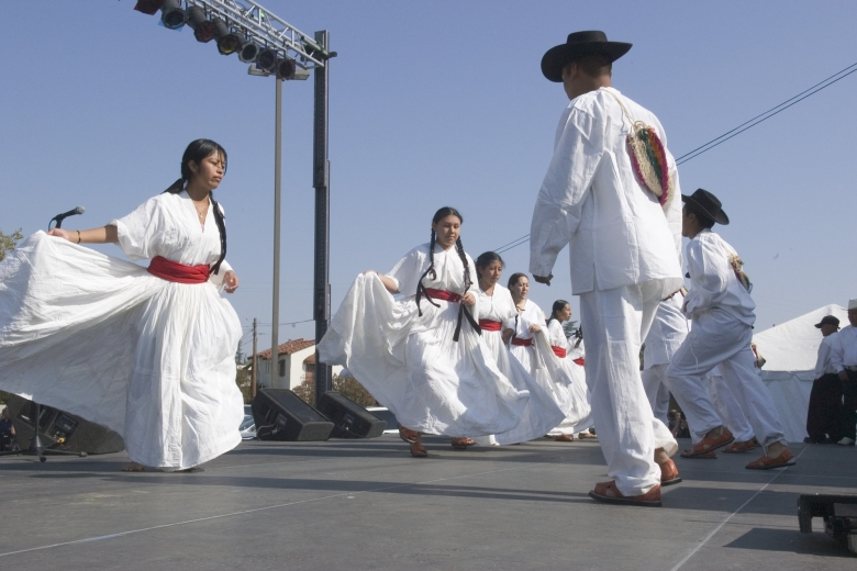 Men and women wearing white clothing dance together.