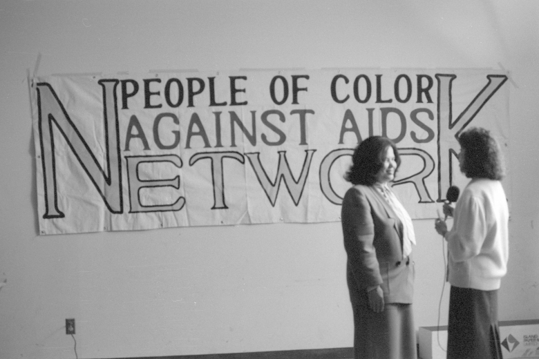 "Two women speak into a microphone in front of a banner on the wall that reads ""People of Color Against AIDS Network."""
