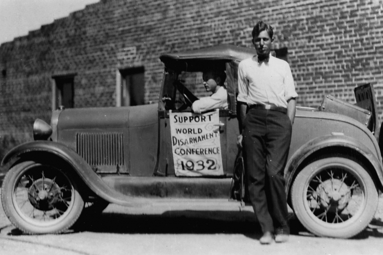 Young man stands next to a car while another man sits in the car. The car has a banner on the side for supporting the 1932 disarmament conference.