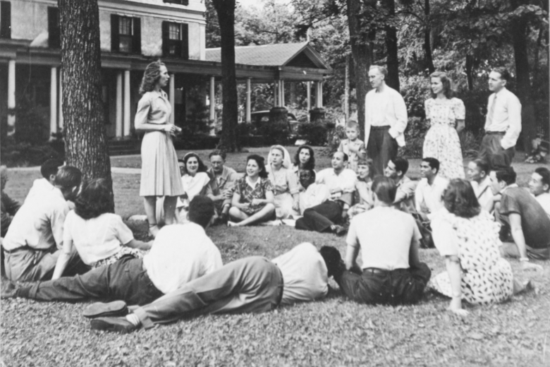 Group of young adults sits and stands together on a lawn, under a tree, with a building in the background.
