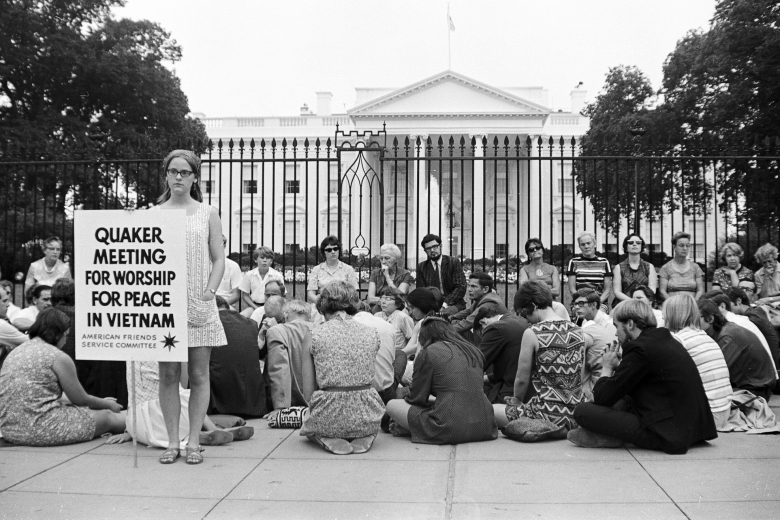 """Group of people seated on the sidewalk, heads bowed in prayer, while one woman stands, holding a sign that reads """"Quaker Meeting for Worship for peace in Vietnam."""""""