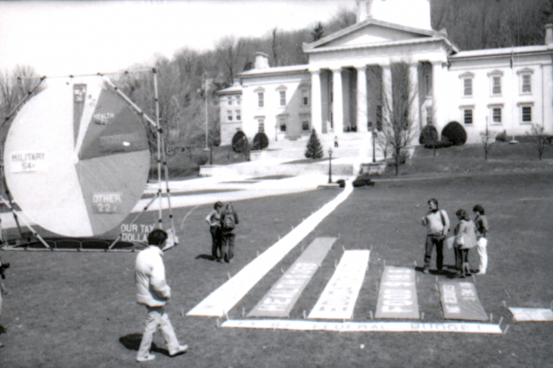 People examine a bar graph and pie chart displayed on the lawn in front of a state government building.