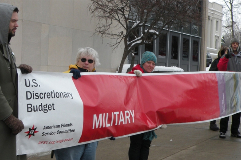 Group of people hold a large banner displaying the percentage of the U.S. discretionary budget spent on the military.