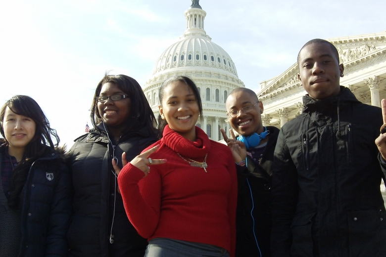 Group of young adults stand in front of government buildings.
