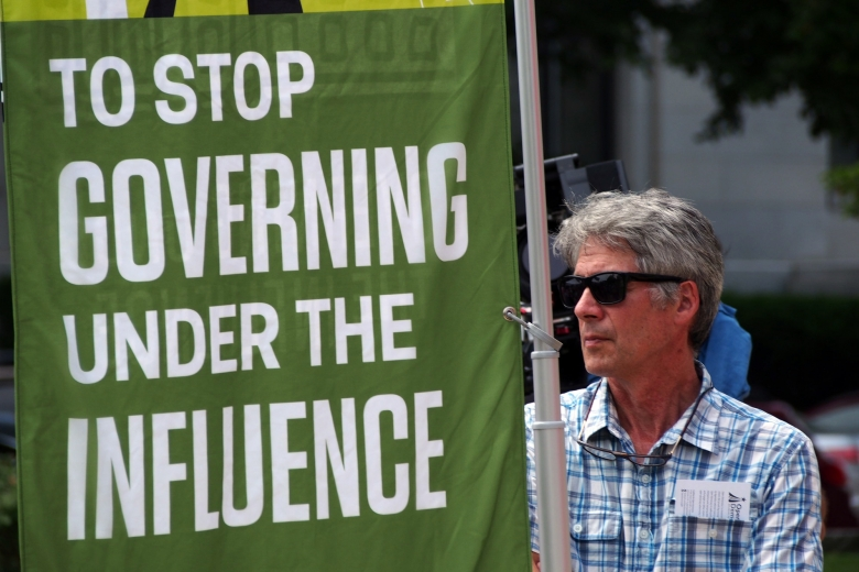"Man holds a banner that reads ""To stop governing under the influence."""