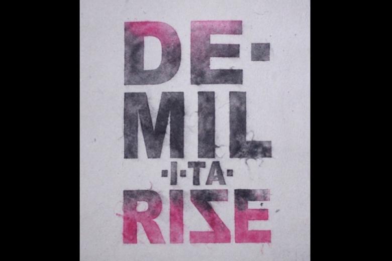 "Poster displays the word ""De-militarize."""