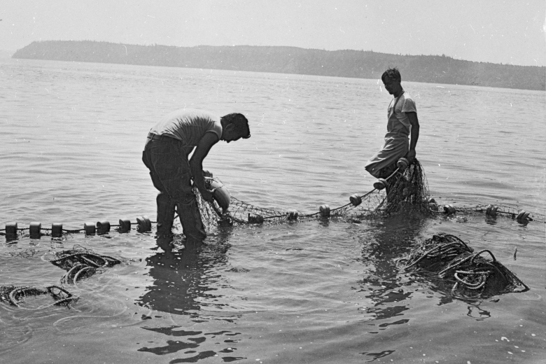 Two people working with fishing nets in a river.