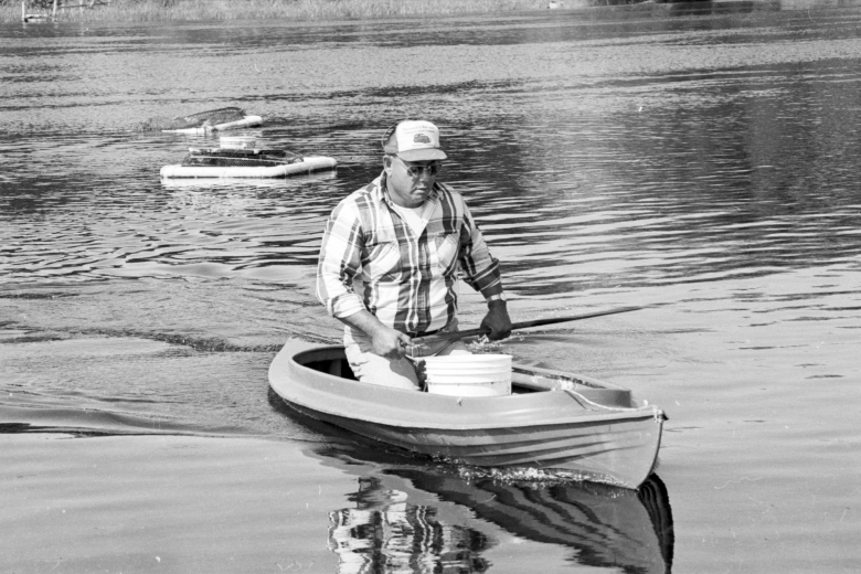 Man kneels in a small boat.