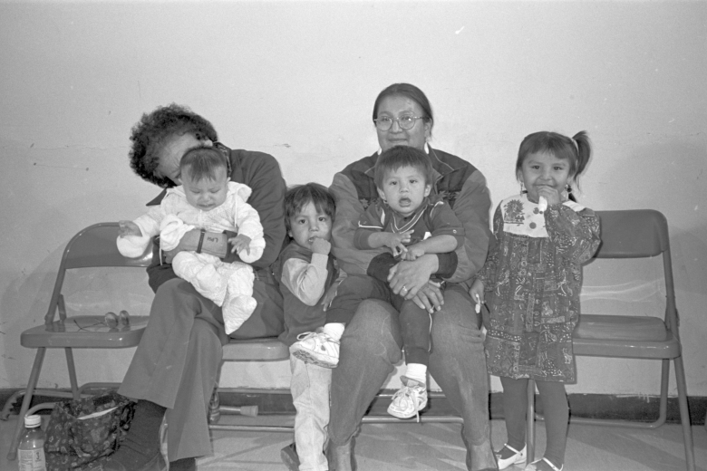 Two adults sit with four children.