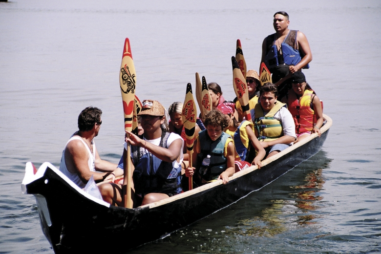 13 people sit and stand in a canoe.