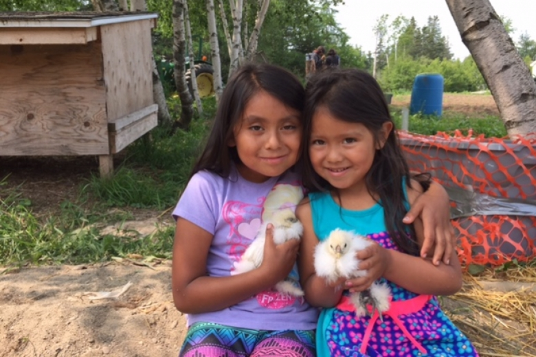 Two girls site next to one another and hold chicks.