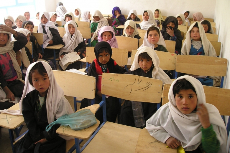 Children sitting at desks in a classroom wearing headscarves.