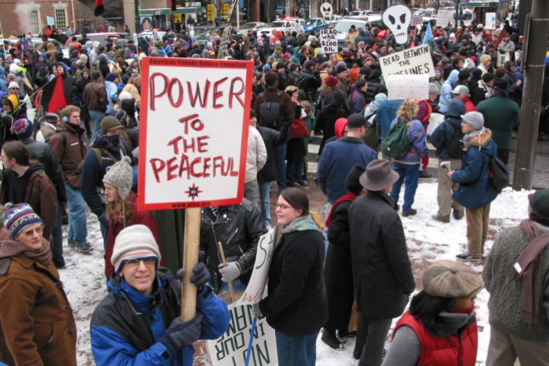 "Group of people stand in protest in a street covered in snow, one person holding a sign that reads ""power to the peaceful."""