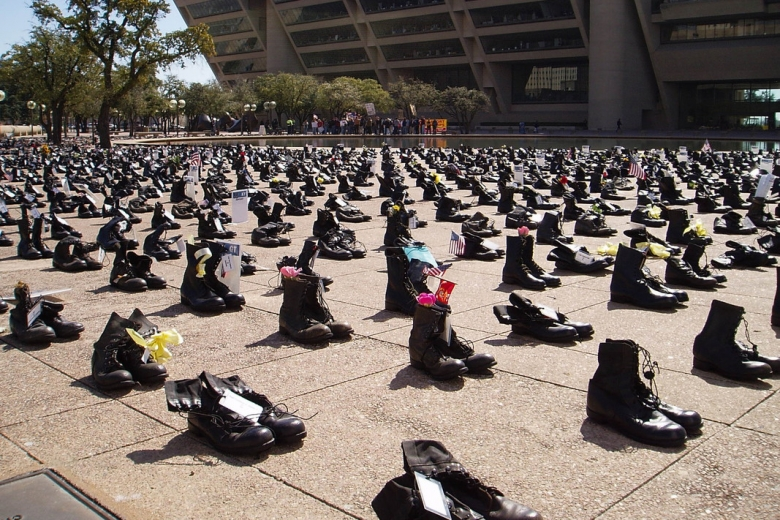 Pairs of boots lined up in rows and columns fill a huge section of sidewalk.