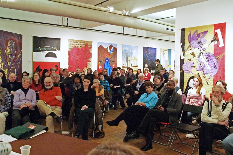 Audience seated in chairs in a room full of large pieces of art look towards the front of the room.